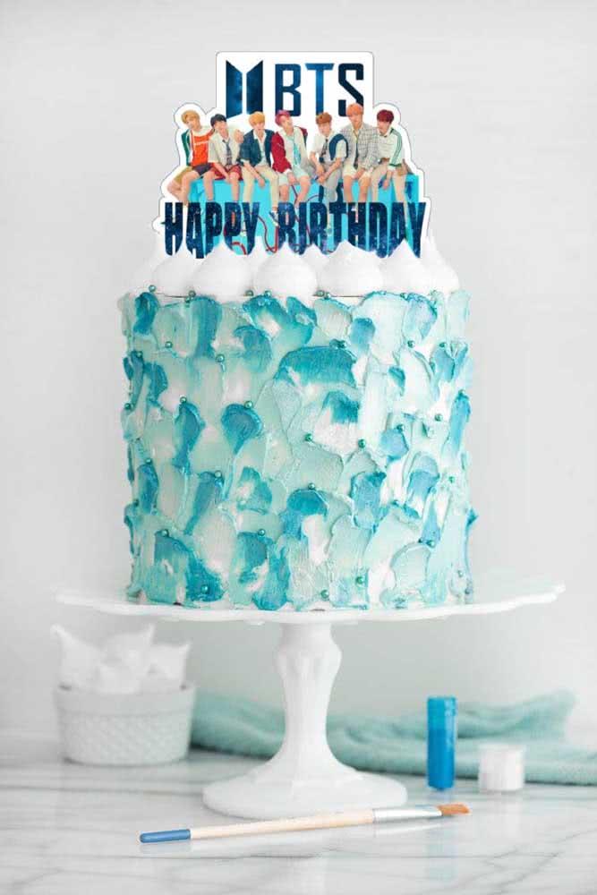Bolo BTS decorado com chantilly em tons de branco e azul. O topo do bolo traz tags com as fotos de todos os integrantes