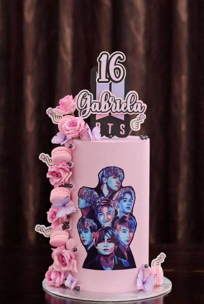 Bolo BTS rosa com direito a uma cascata de flores e foto do grupo