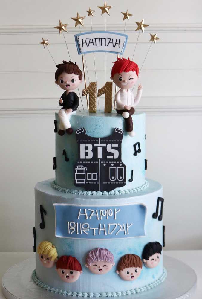Aqui, o bolo BTS foi decorado com pasta americana, tem dois andares e bonequinhos de biscuit para representar os meninos do grupo
