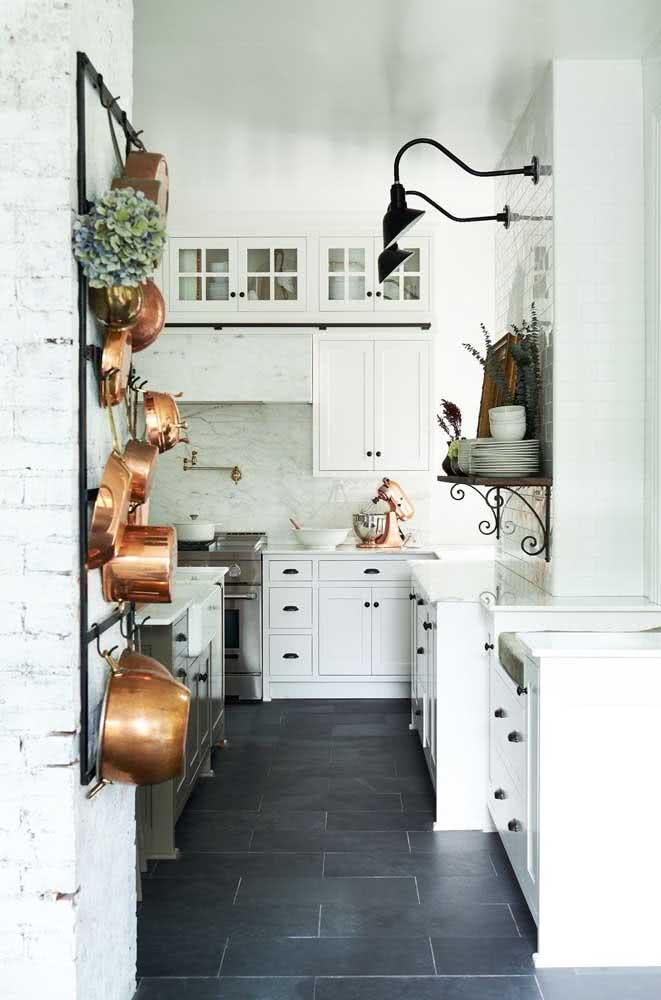 A cozinha branca de marcenaria clássica ganhou um toque de modernidade com o piso de ardósia