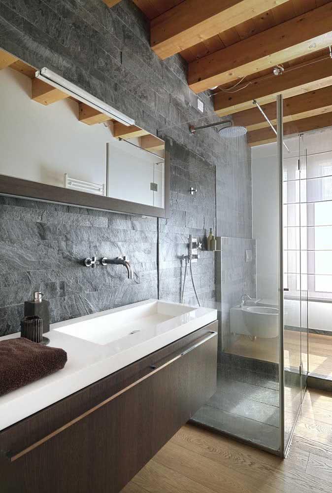 Ardósia rústica no banheiro combinando com as vigas expostas de madeira