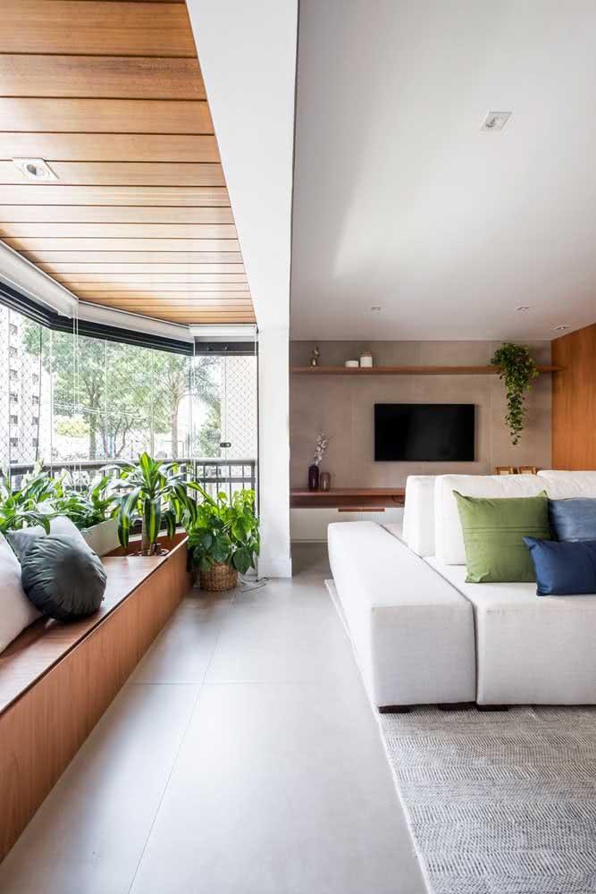 Já essa varanda integrada com a sala traz um sofá banco