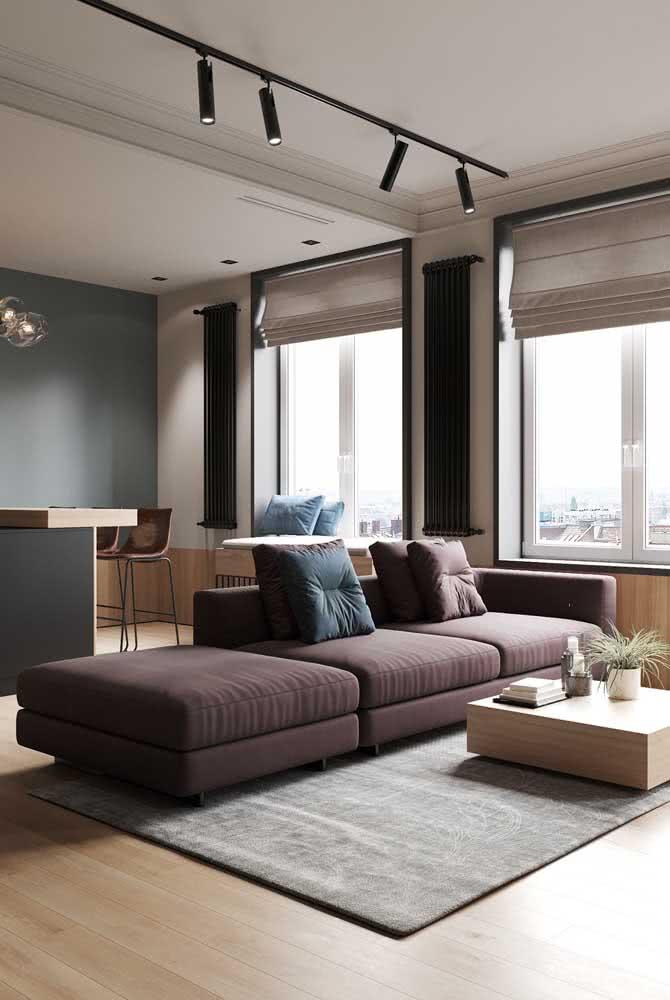 Luminária de trilho na sala de estar com spots voltados para o sofá
