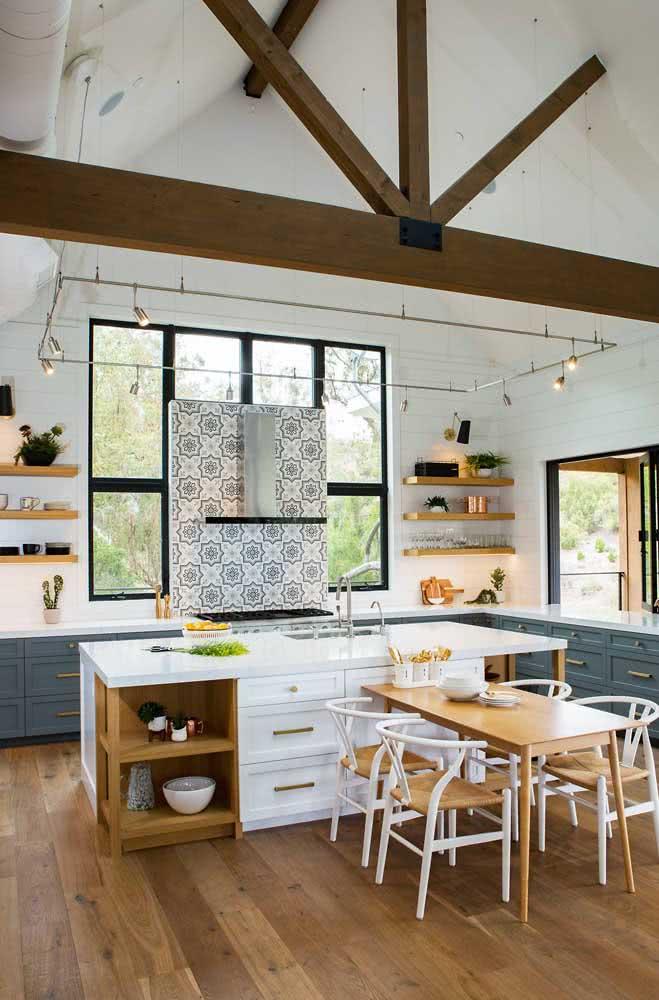 A cozinha de pé direito alto apostou em uma luminária de trilho formando um quadrado