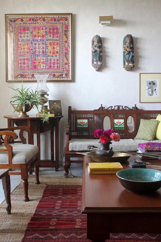 Nessa sala de estar, a decoração indiana aparece no tapete, nos móveis talhados em madeira e nas imagens de deuses na parede