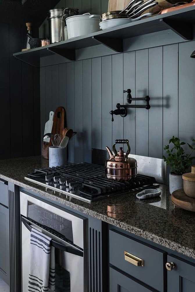 Granito cinza dividindo espaço com os armários de tom azul escuro