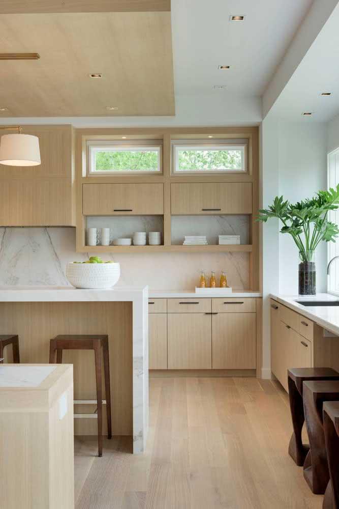 Cozinha sob medida com balcão em cores claras e aconchegantes