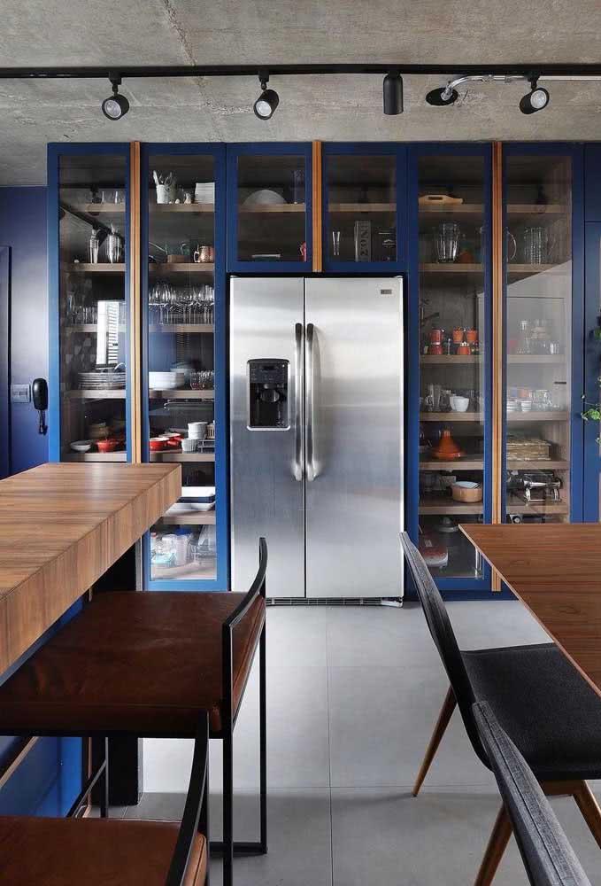 Cozinha sob medida em estilo industrial com detalhes em azul e teto de cimento queimado