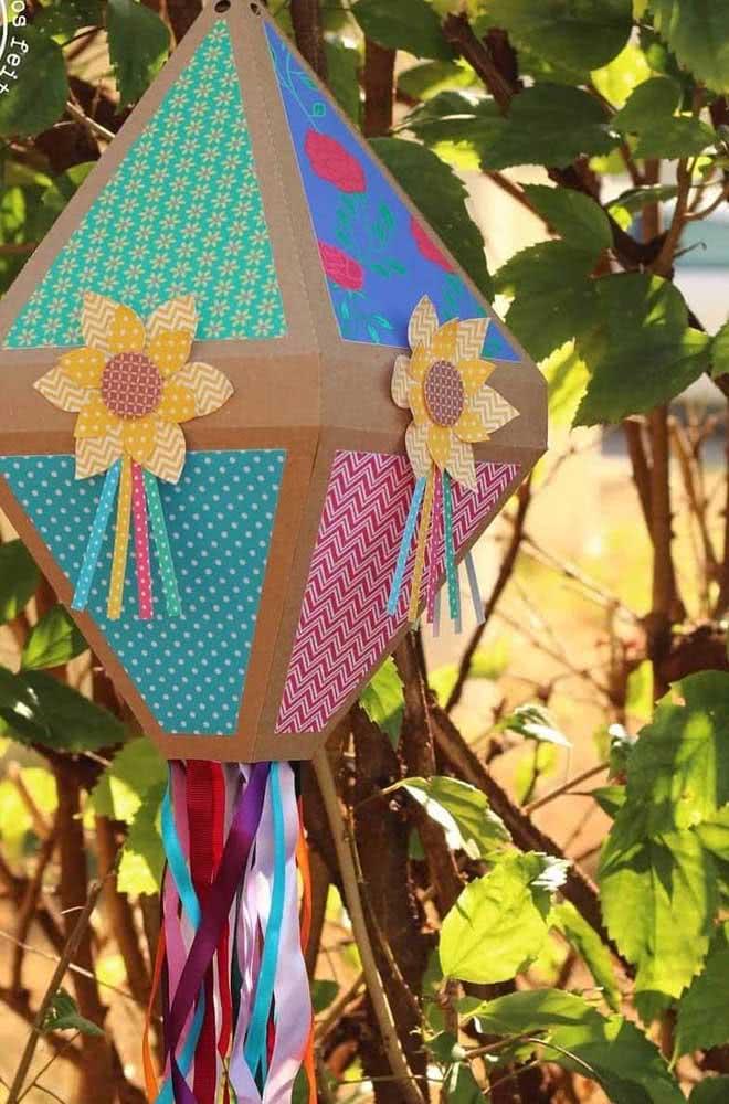 Já aqui, a dica é fazer um balão de festa junina de papelão decorado com tecido