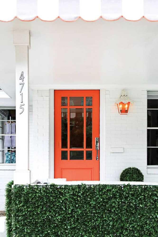 Fachada branca em contraste com a porta Coral