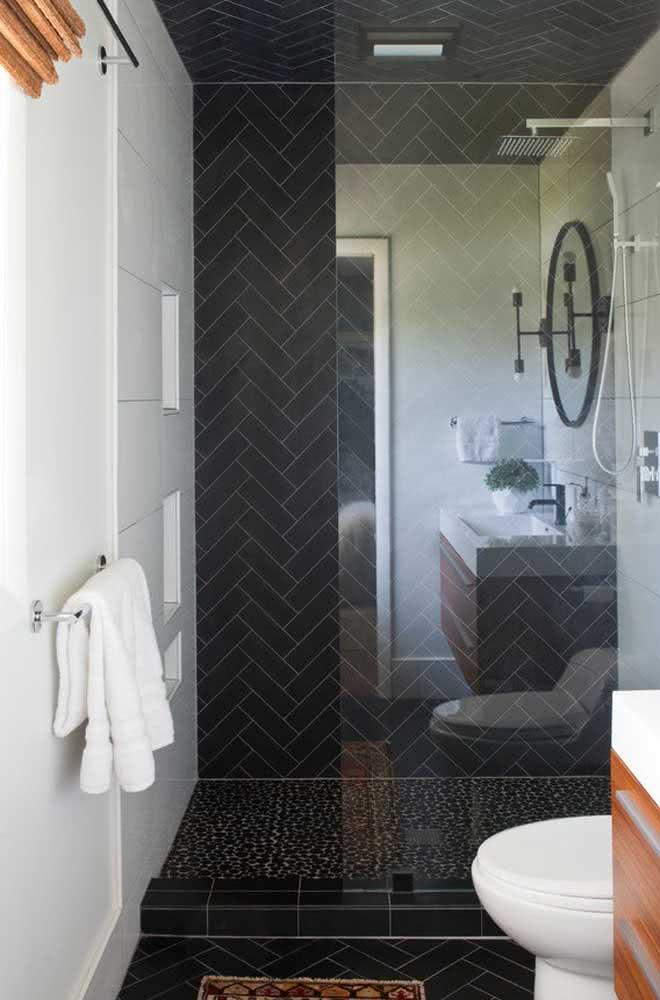 Piso de seixo preto para a área do banho. Na parede, azulejos de metrô