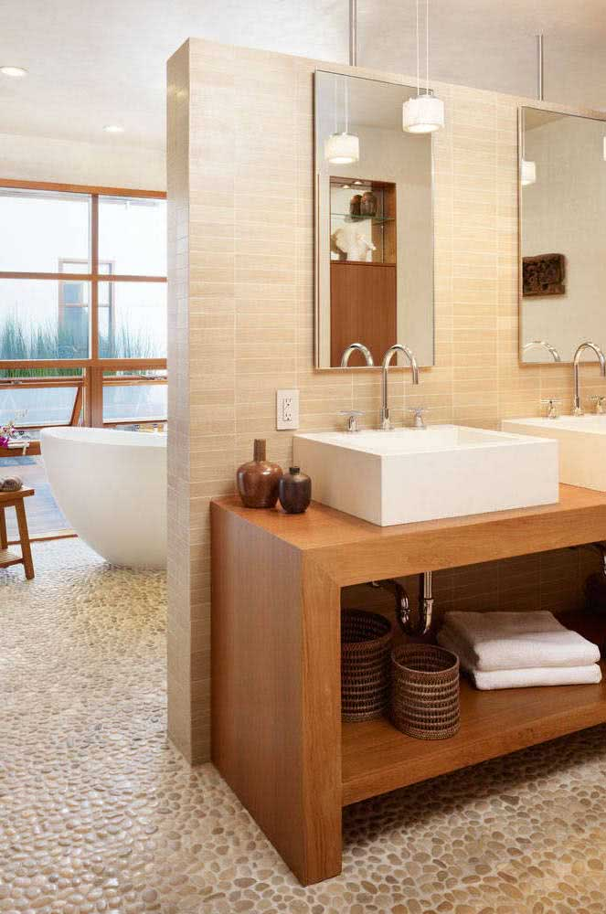 Piso de seixos beges combinando com o restante da decoração do banheiro