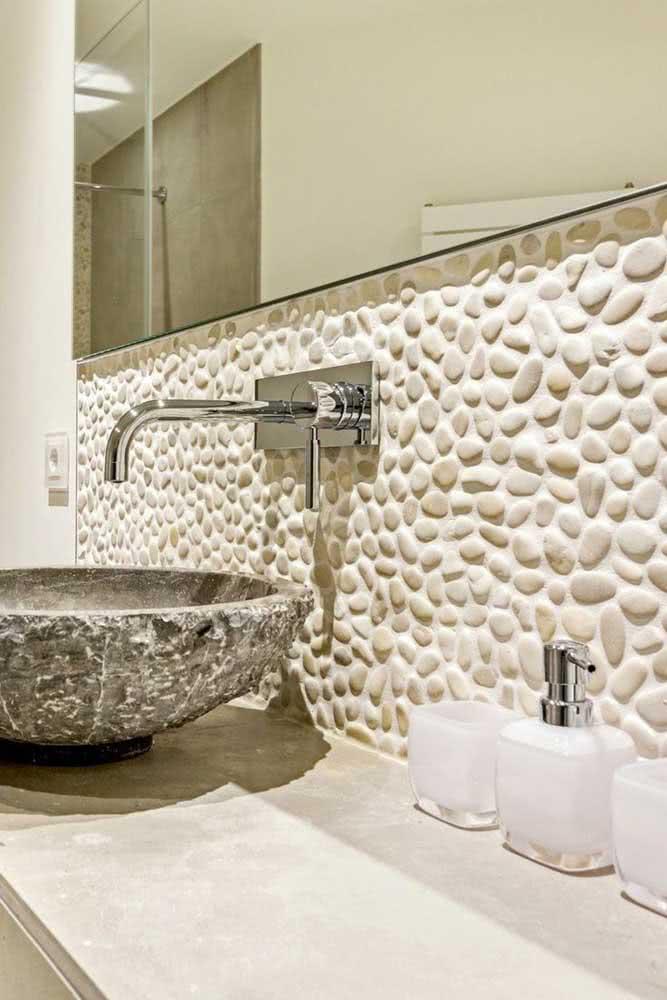 Banheiro elegante e rústico decorado com seixos brancos e pia de pedra