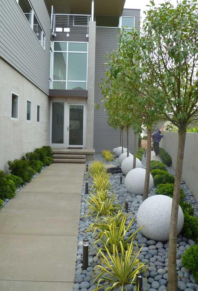 Um mini jardim decorado com seixos cinza da mesma cor da pintura da fachada