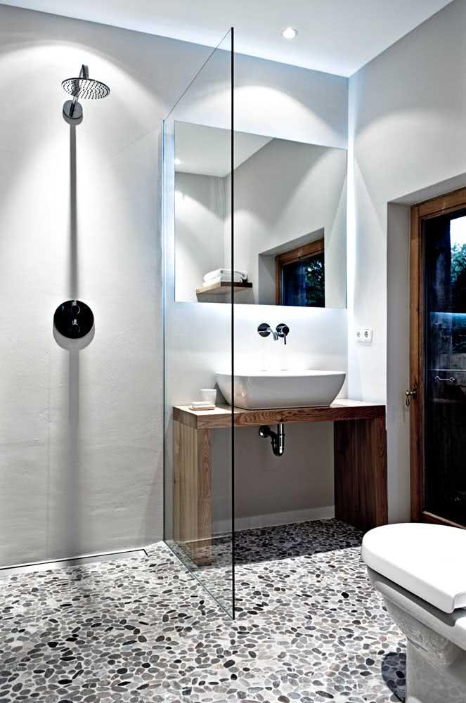 Banheiro moderno e minimalista decorado com piso de seixos branco e preto