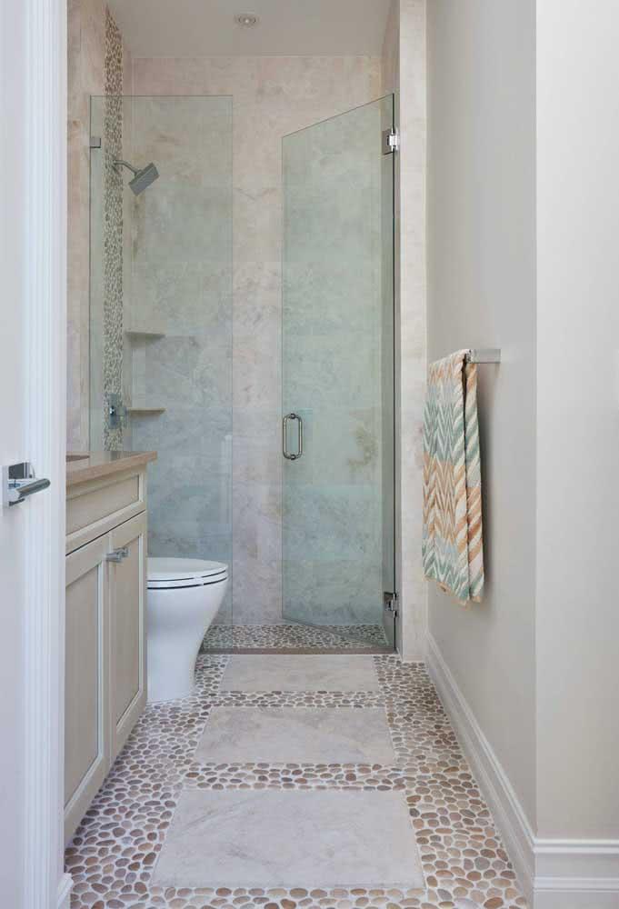 Banheiro pequeno valorizado pelo piso de seixos claros