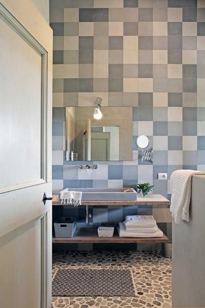 Uma composição inusitada, mas que deu super certo: piso de seixo com revestimento de azulejos quadriculados