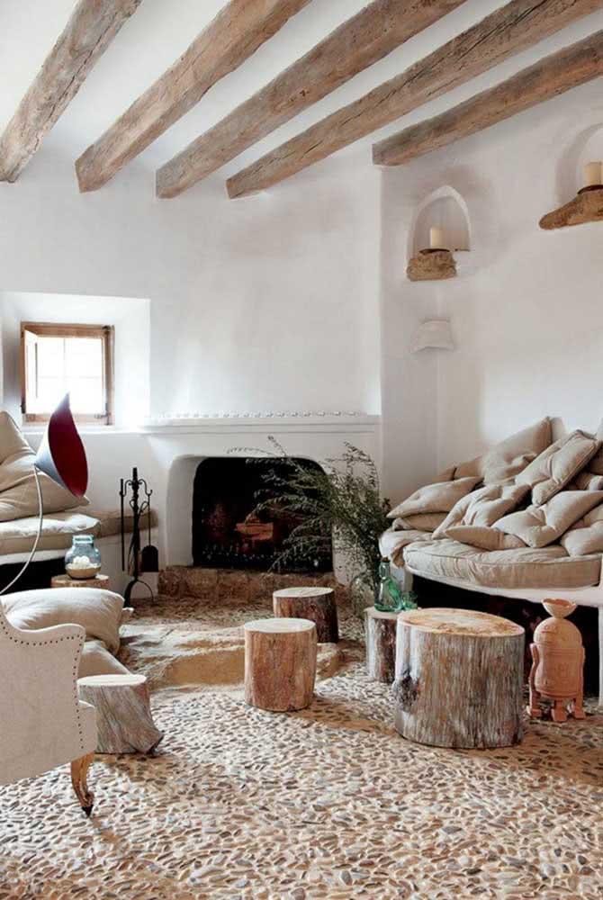 Nessa sala de estar, o destaque vai para o piso de seixos combinando com o estilo rústico dos móveis