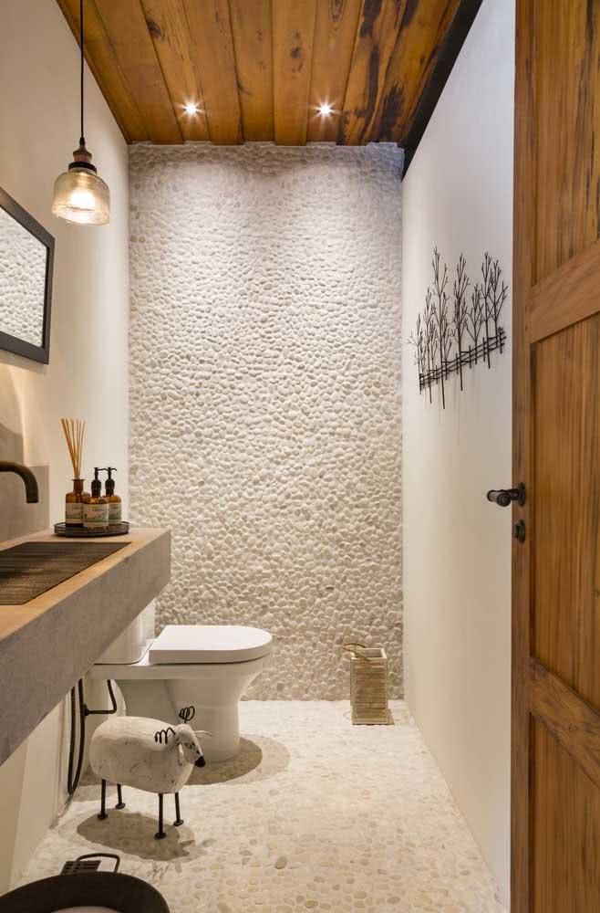 Capriche na iluminação para destacar a parede de seixos do banheiro