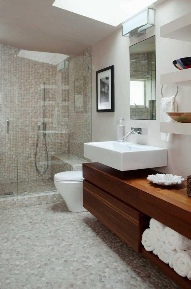 Banheiro clean e moderno com piso de seixos e pastilhas na área do box