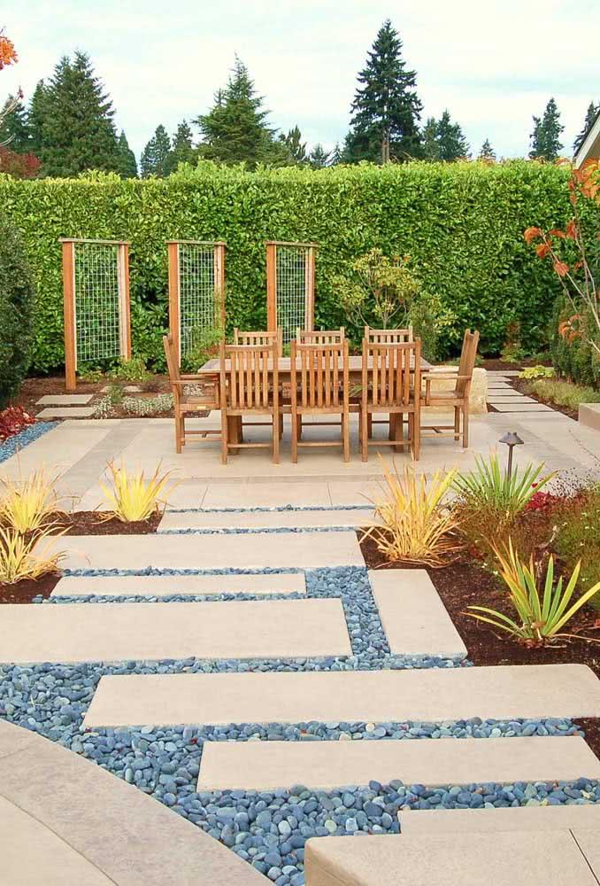Seixos e placas de cimento formam o caminho até o jardim da casa
