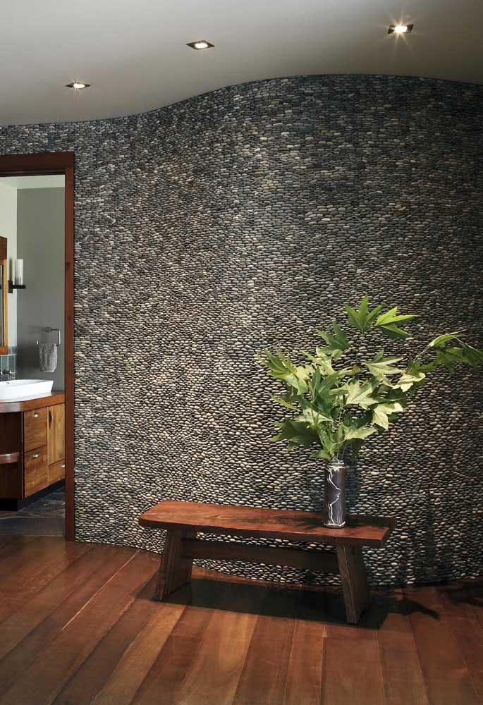 Seixos pretos para trazer sofisticação a essa parede de corredor ondulada. A iluminação indireta valoriza ainda mais as pedras