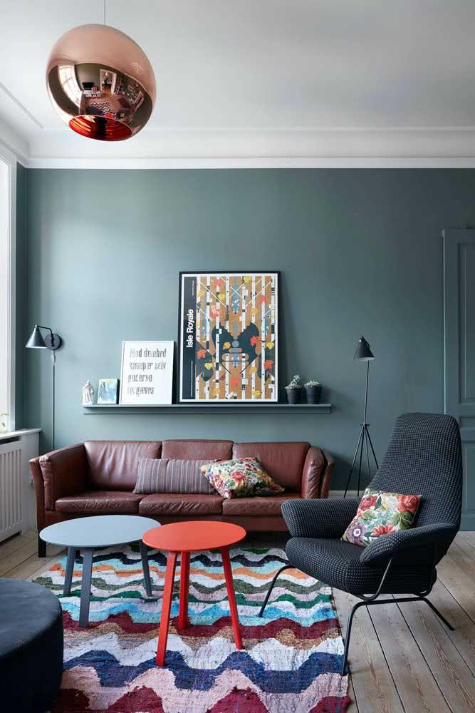 Quadros na parede do sofá é um clássico, mas expostos sobre uma prateleira é novidade