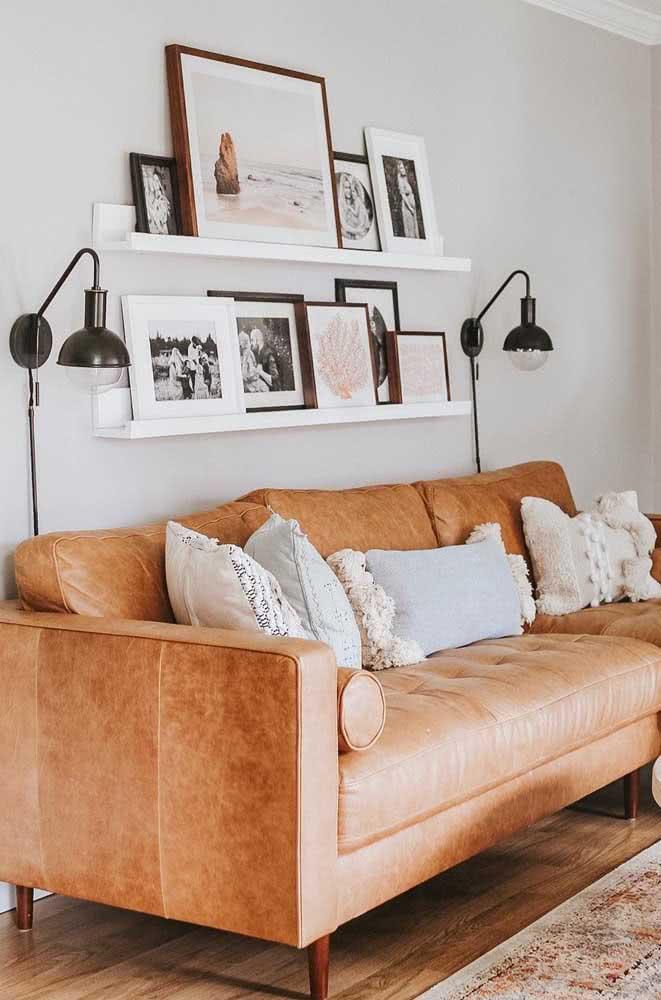 Sobre o sofá, as prateleiras para quadros organizam e expõe fotos pessoais e fotos artísticas.
