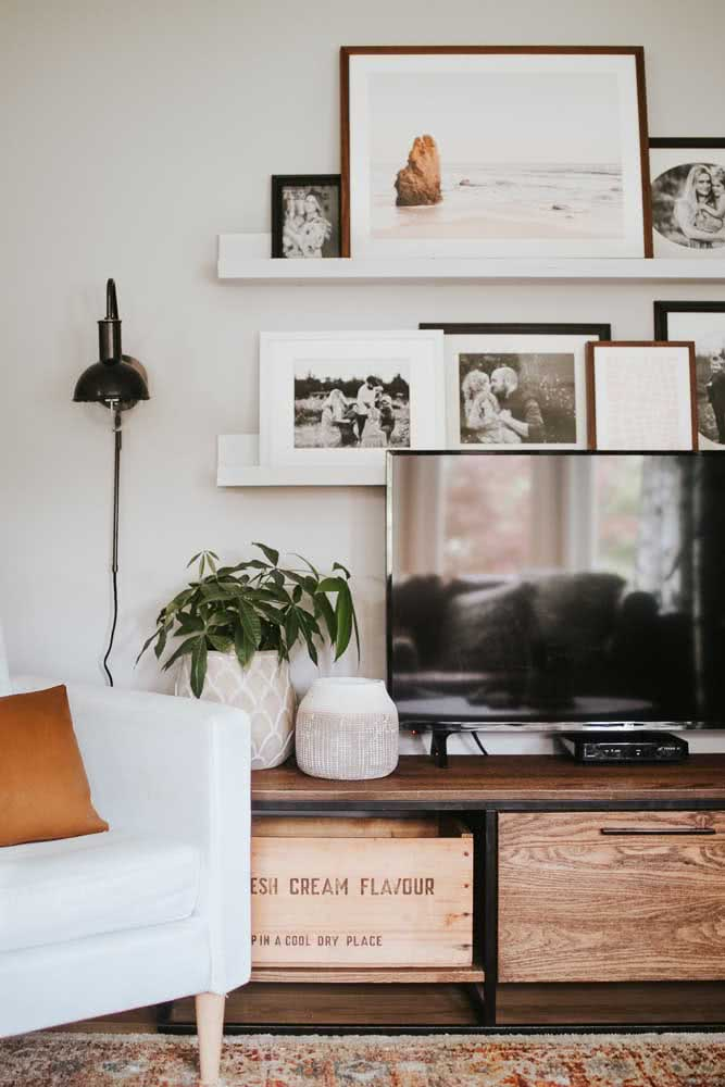 Prateleira para quadros na parede da TV. Repare que os quadros foram organizados de maneira sobreposta