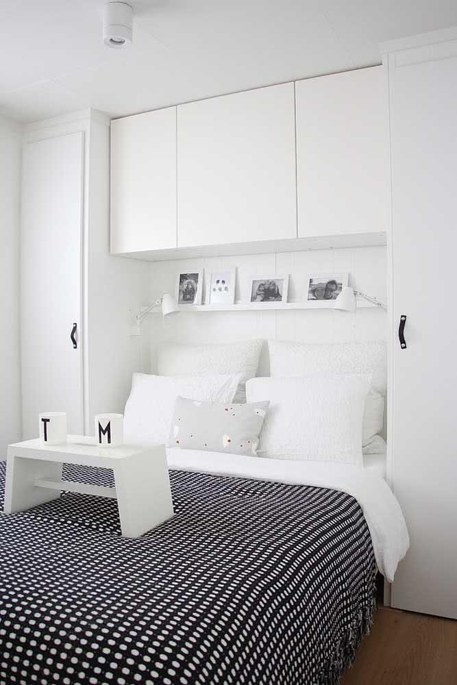 Já nesse quarto de casal, a prateleira para quadros branca integra o projeto do armário embutido