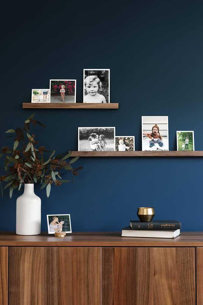 Uma parede azul para garantir todo o destaque que a prateleira para quadros de madeira precisa