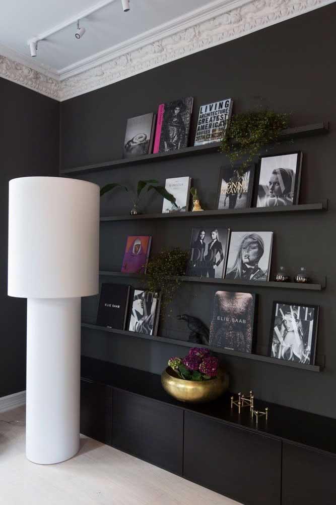 Nessa sala sofisticada, no entanto, a opção foi pela prateleira preta que se camufla na parede da mesma cor