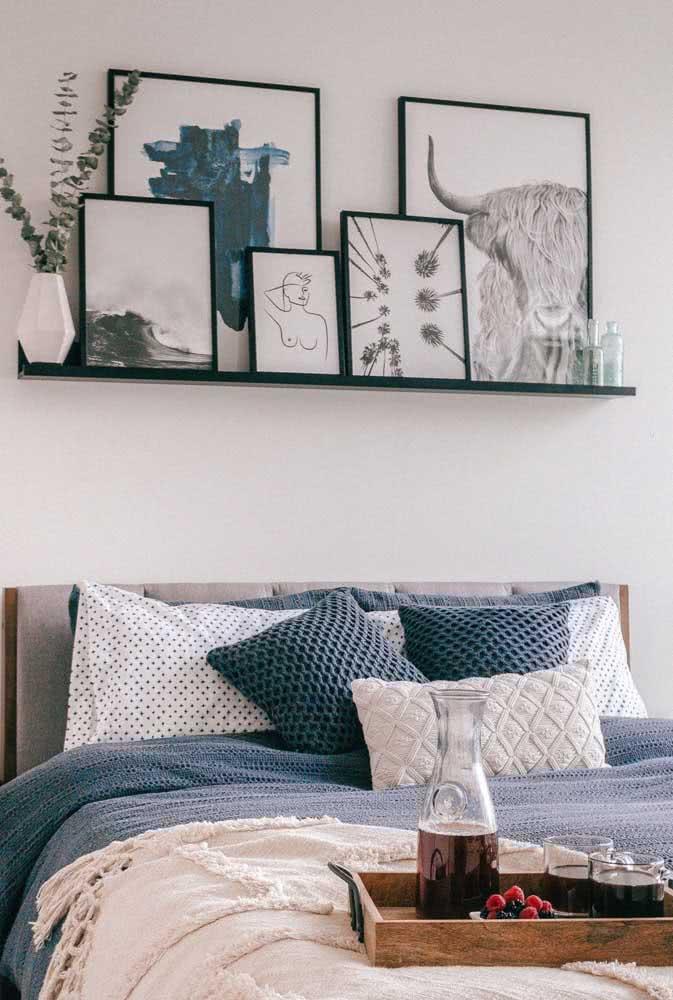Uma prateleira para quadros do tamanho exato da cama. Sobre ela, quadros de layout semelhantes, mas em dimensões diferentes