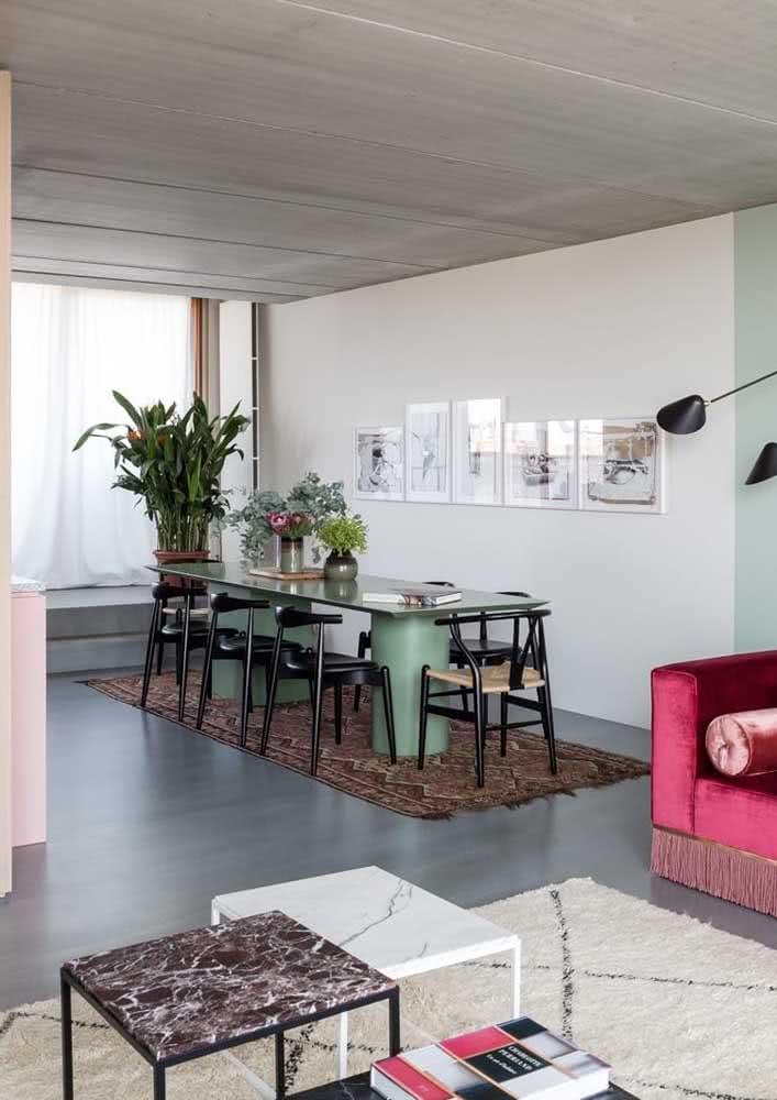 Decoração de sala de jantar grande com tapete, quadros e plantas