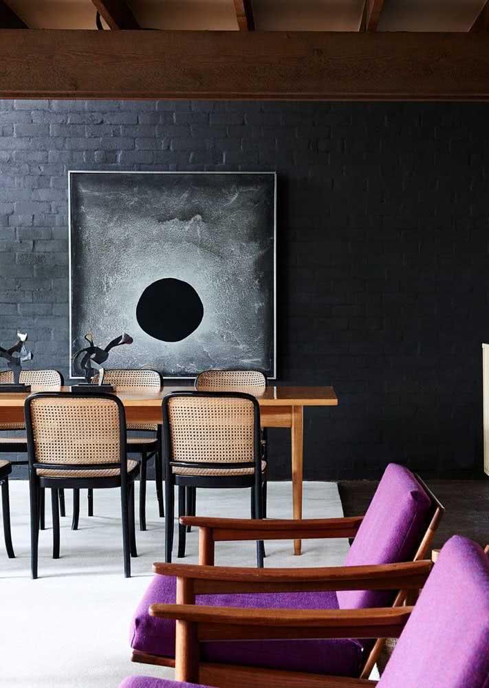 Cadeira de palhinha e parede de tijolos são o destaque dessa sala de jantar moderna