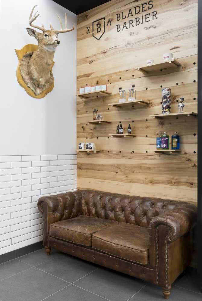O sofá de couro e o painel de madeira garantem a personalidade dessa barbearia