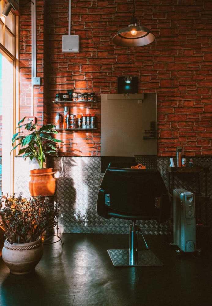 Decoração de barbearia retro com parede de tijolinhos, plantas e cimento queimado