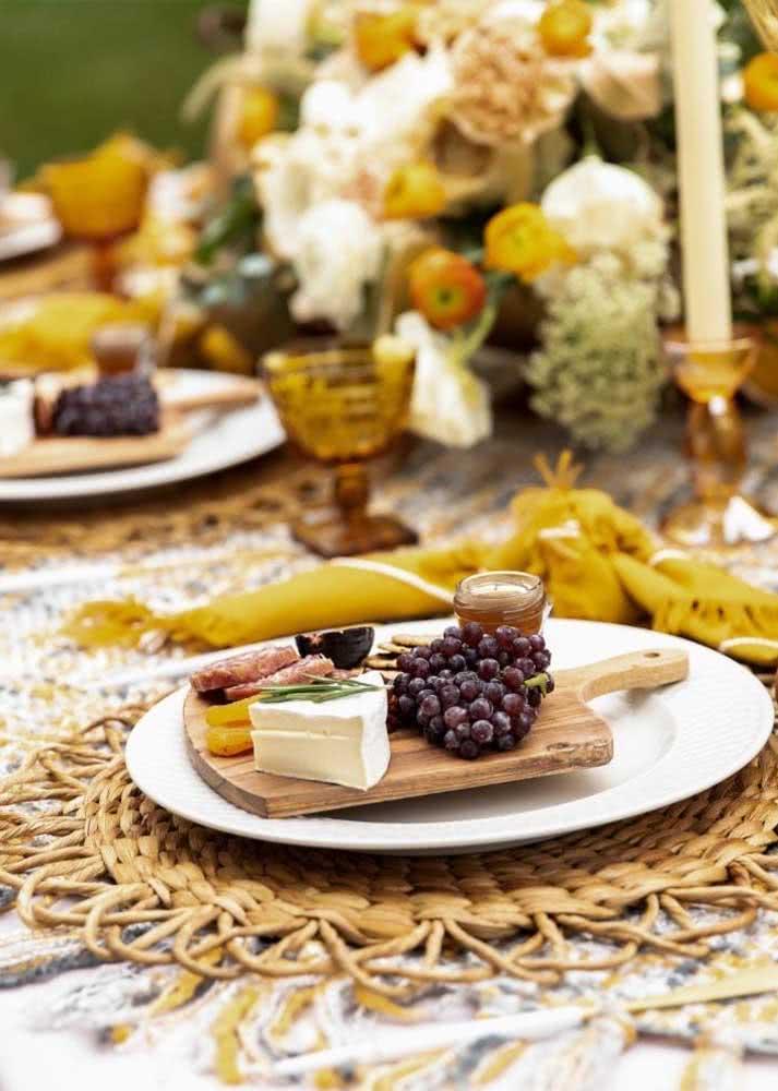 Aqui, cada prato individual ganha uma mini tábua com frios, frutas, petiscos e geléia.