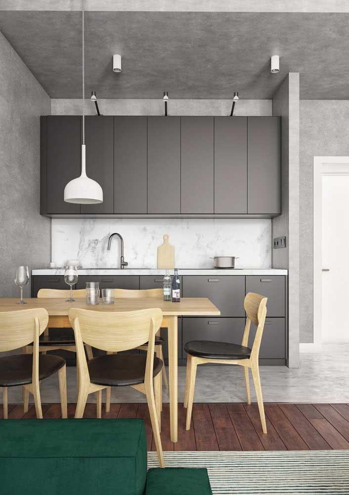 Cozinha com mesa de jantar e parede de concreto.