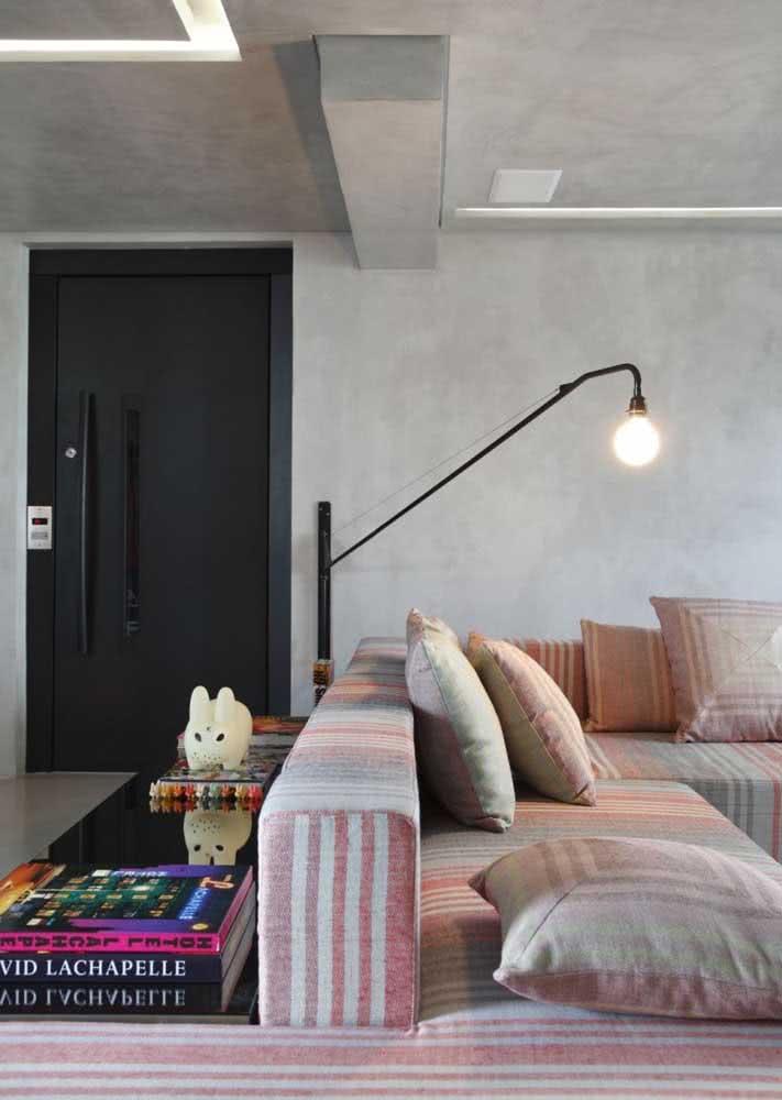 Sala de estar grande com sofá com concreto aparente na parede e no teto.