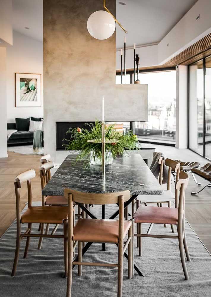 Mesa de jantar em sala com coluna de lareira de concreto ou cimento queimado.