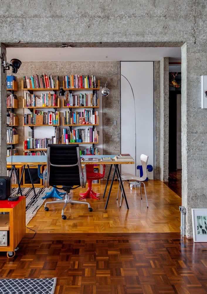 Sala de estar integrada ao espaço da leitura e home office com paredes de concreto.