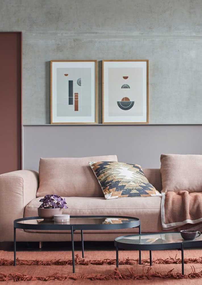 Sala de estar com sofá com tecido salmão e parede de cimento queimado na parte de trás.