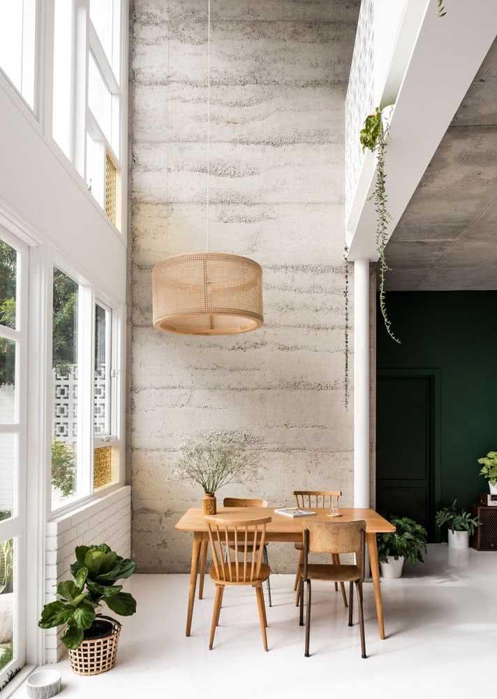 Sala de jantar com pé-direito alto grande e parede de concreto.