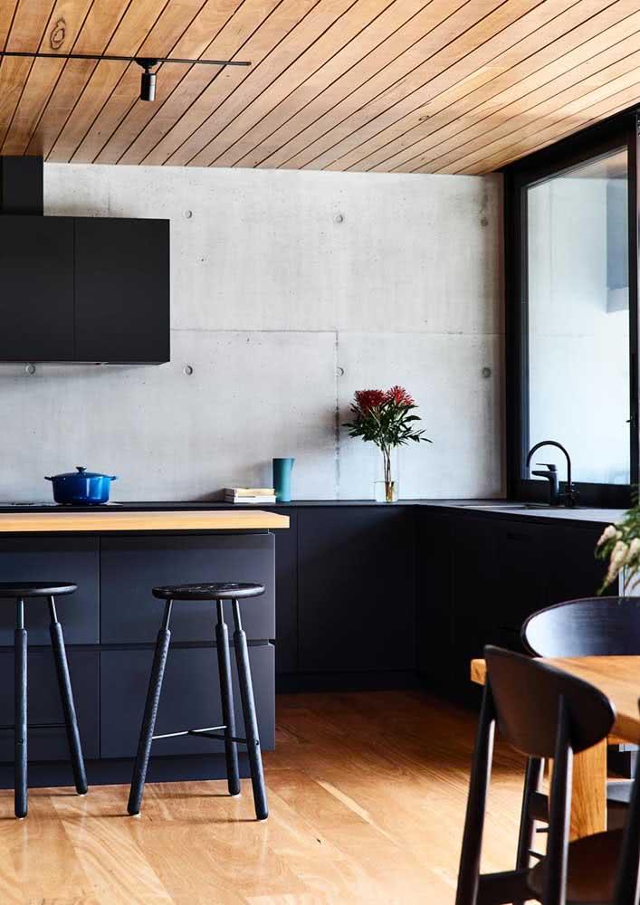 Cozinha com móveis planejados na cor preta, concreto aparente e madeira no piso.