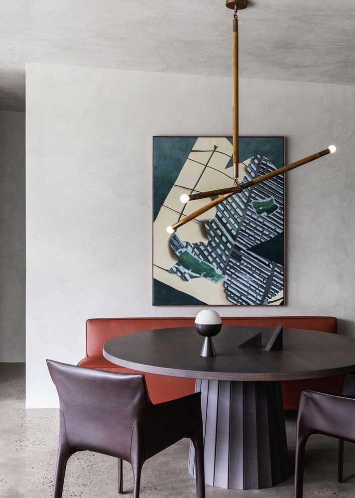 Sala de jantar com mesa redonda e parede de concreto aparente.