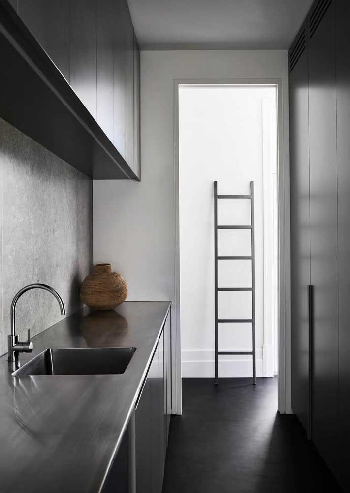 Cozinha toda pretinha com parede de cimento queimado entre a bancada e os armários.