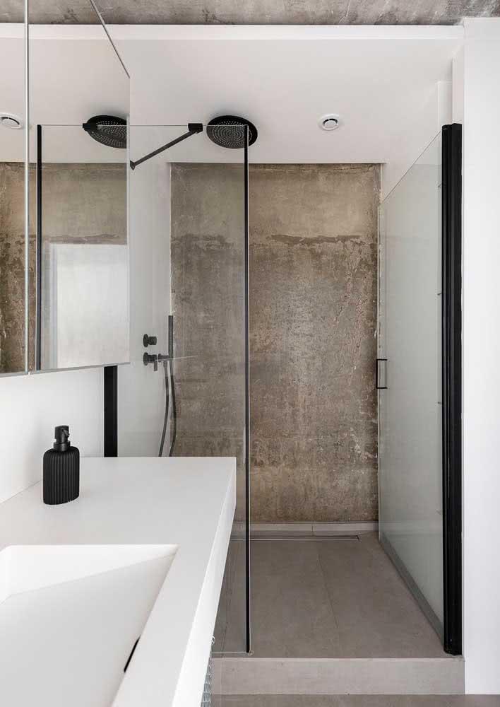 Banheiro amplo com parede de concreto na área do box.