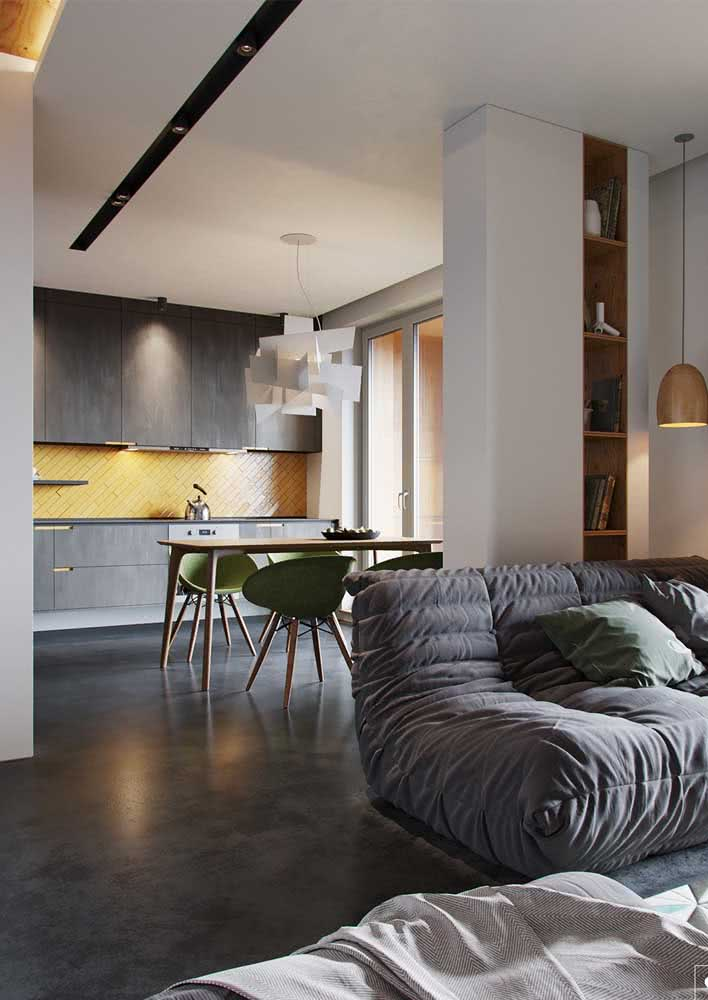 Cozinha e sala de estar integradas com piso de cimento queimado.