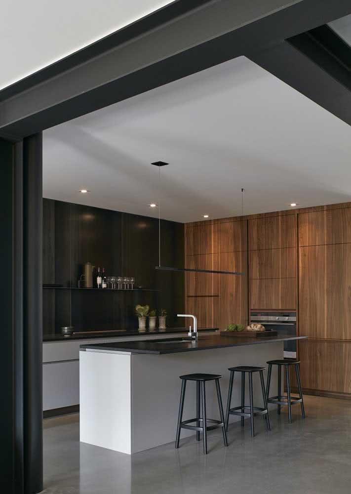 Cozinha com ilha central e bancada de granito preto absoluto.